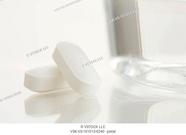 Close-up of painkiller and glass of water