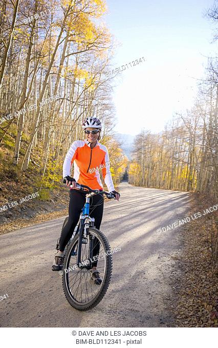 Hispanic woman riding dirt bike on path