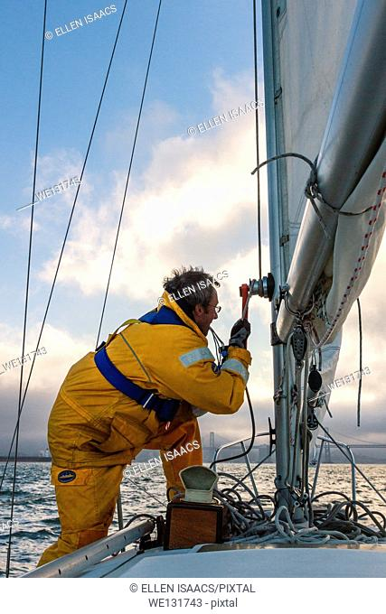 Sailor in yellow foul weather gear securing the halyard after raising the mainsail as he heads into cloudy weather in his sailboat