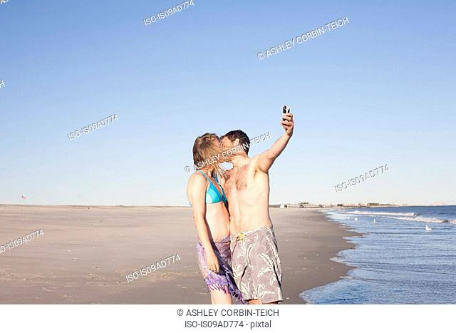 Couple taking self portrait on beach, Breezy Point, Queens, New York, USA