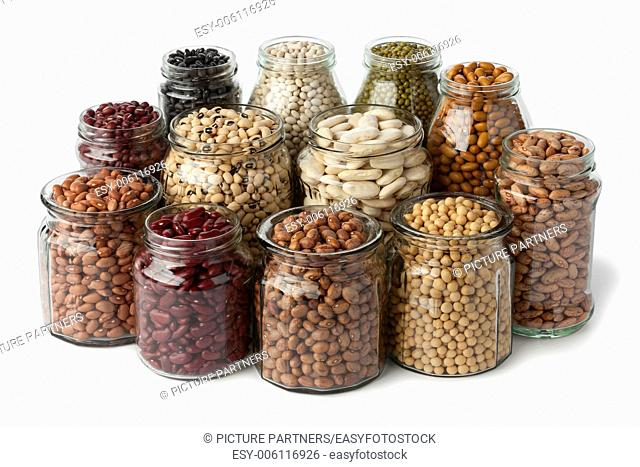 Glass pots with dried beans on white background