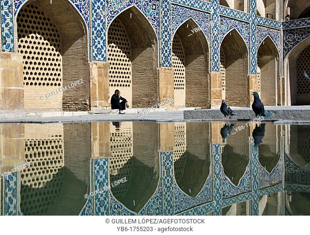 Man sitting under the arches of the Jameh Mosque of Isfahan, Iran