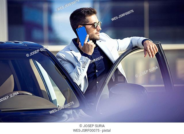 Young businessman standing at his car, talking on the phone