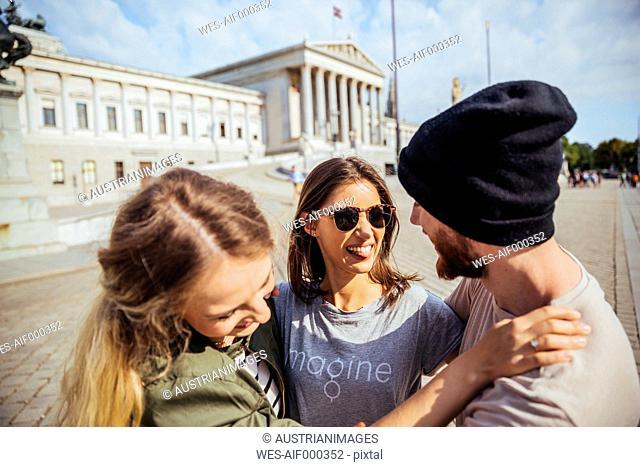 Austria, Vienna, three friends having fun in front of the parliament building