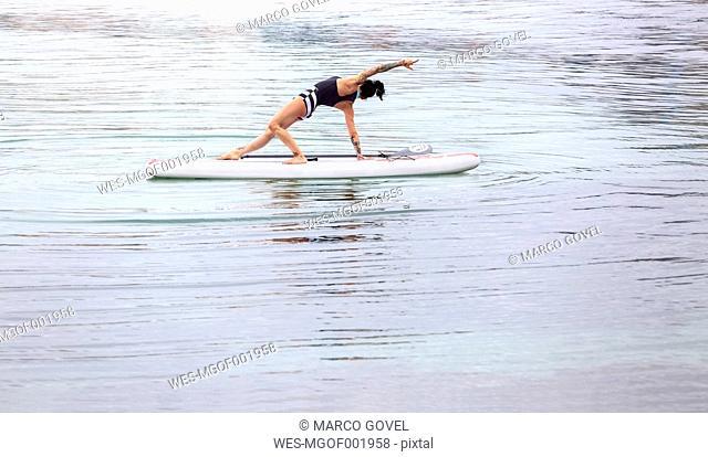 Woman practicing paddle board yoga