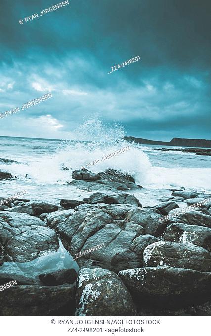 Dark storm clouds and huge waves splash the rocky coastal shores of a fierce seascape. Cloudy Bay, Bruny Island, Tasmania, Australia