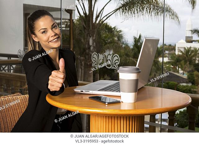 Pretty adult businesswoman with laptop at table holding thumb up smiling at camera against tropical palms in window