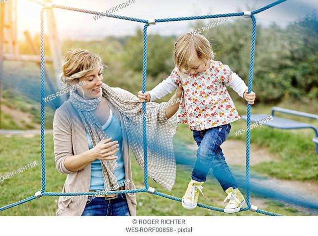 Girl on playground in climbing net supported by mother