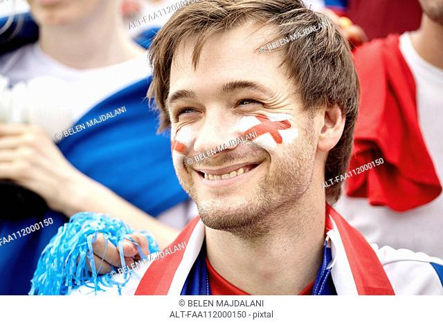 British football fan smiling cheerfully at match, portrait