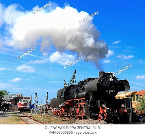 An old steam locomotive from production series 52 rolls into the traditional railway depot at the railway association festival inStassfurt, Germany