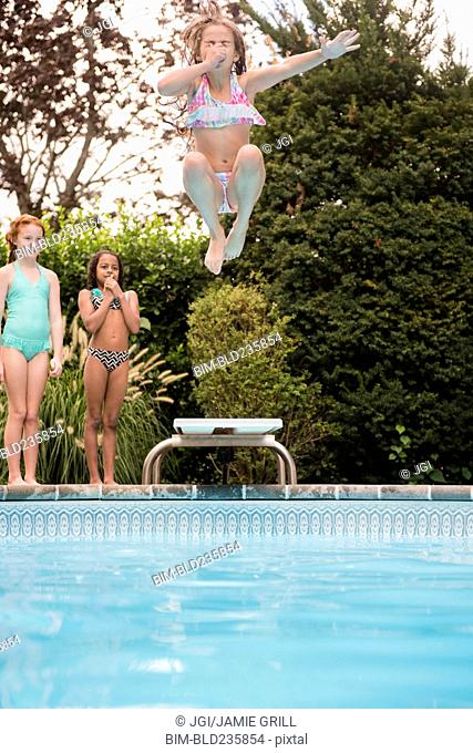Girl holding nose jumping off diving board into swimming pool
