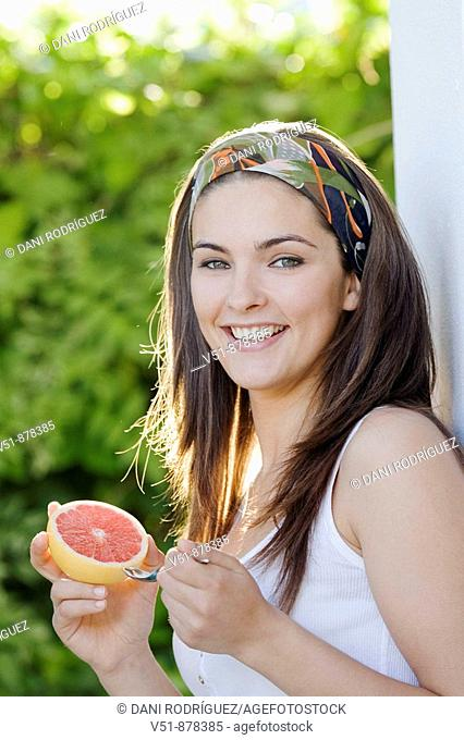 Woman with a piece of fruit smiling and looking at camera