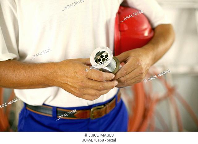 View of plumber holding hose with red hard hat under his arm