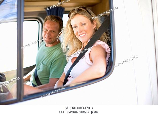 Smiling couple driving RV