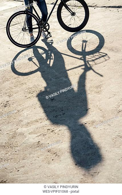 Close-up of man with commuter fixie bike on concrete slab
