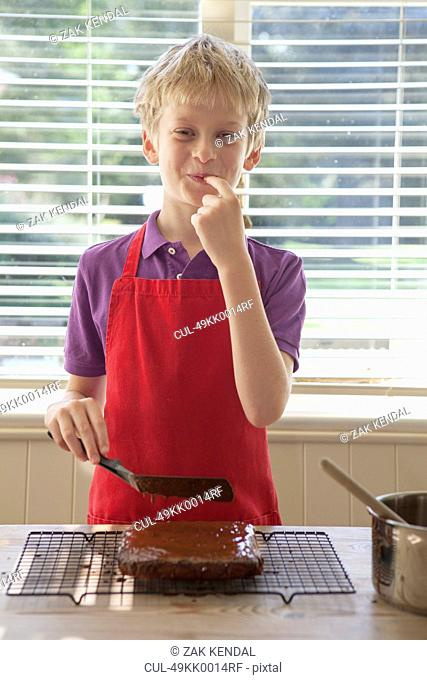 Boy tasting cake frosting in kitchen