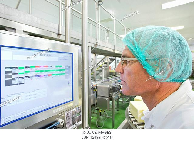 Machine operator watching computer monitor in cheese processing plant