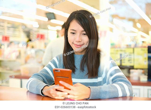 Woman using cellphone at coffee shop