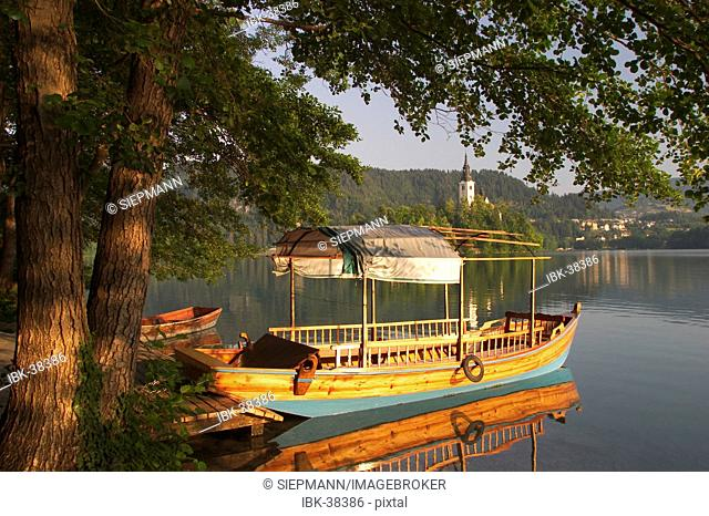 Lake Bled with boat and island Otok in the morning - Slovenia - glacial lake in the extreme northwestern region of Slovenia, situated northwest of Ljubljana