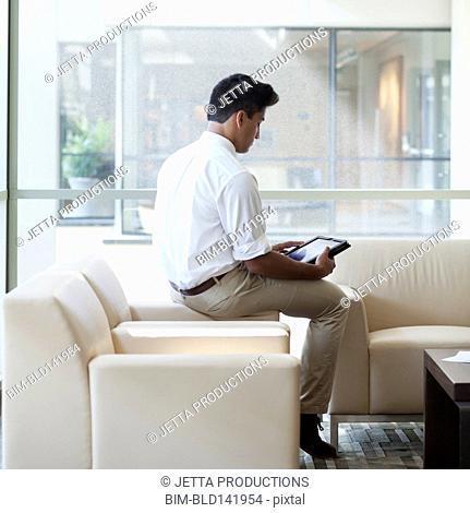 Indian businessman using digital tablet in office lobby