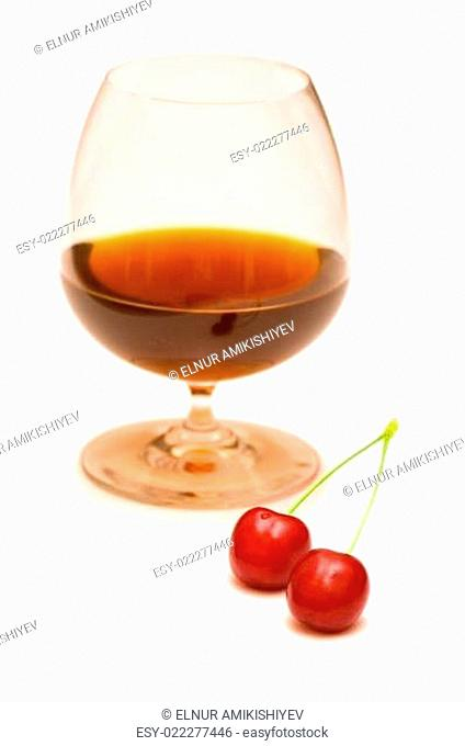 Glass of wine and two cherries on white