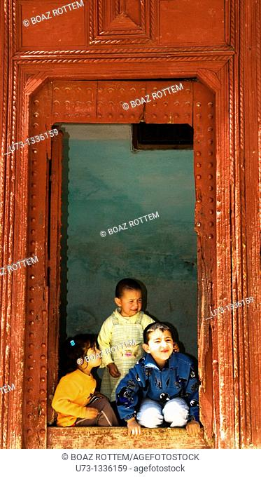 Cute Moroccan children sitting by the door of their home in Sefrou
