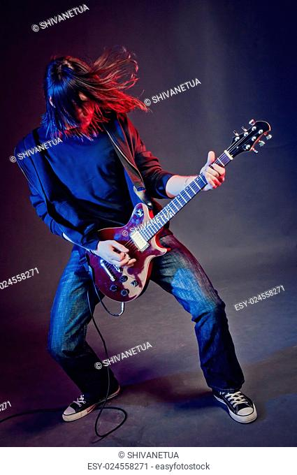 Rock-star perfoming loud music on red electric guitar