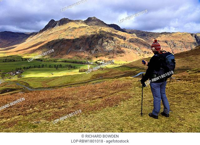 England, Cumbria, Langdale. A woman using a handheld GPS device whilst walking in the hills above the Langdale valley
