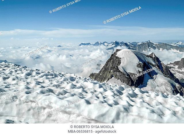 Low clouds around the snowy peak of Mount Ciarfaron. Graian Alps Gran Paradiso National Park Aosta Valley Italy Europe