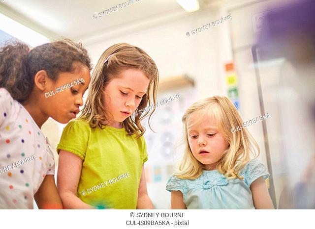 Primary schoolgirls looking down in classroom