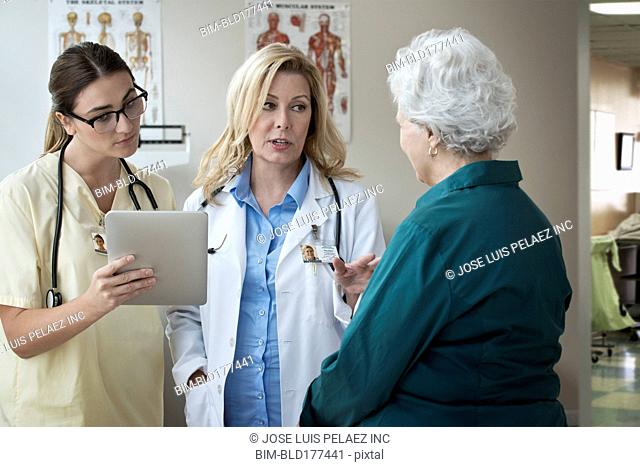 Caucasian doctor and nurse talking to patient