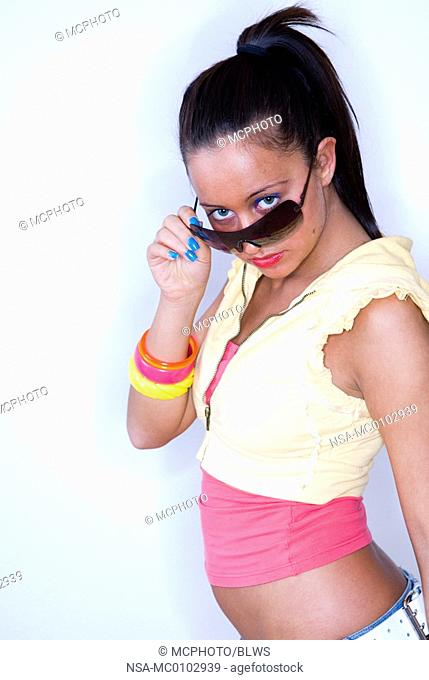 young woman looking over the top of her sunglasses