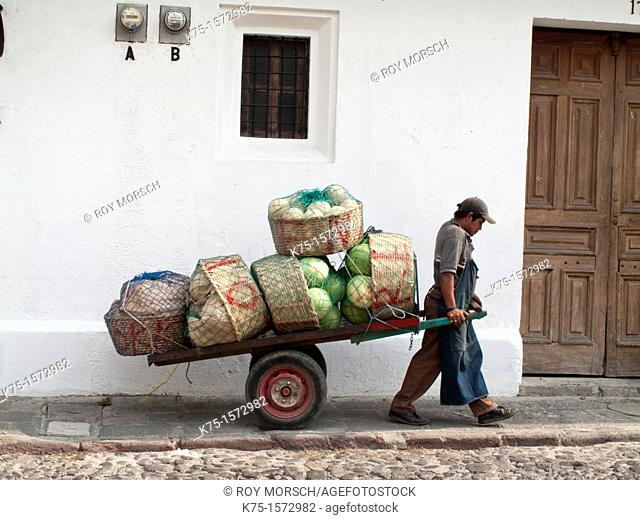 Man pulling delivery cart of watermelons