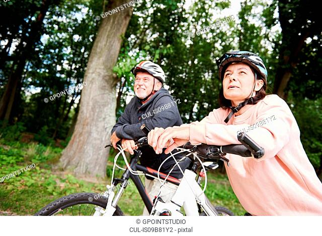 Mature couple walking along rural pathway with bicycles, looking at view