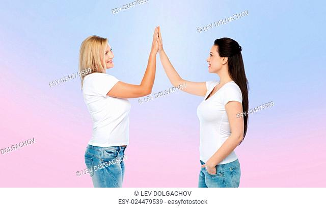 friendship, diverse, body positive, gesture and people concept - group of happy different women in white t-shirts making high five over rose quartz and serenity...