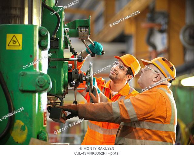 Engineer teaching apprentice in factory