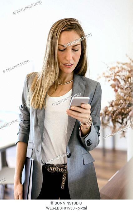 Businesswoman checking messages on her smart phone, looking worried