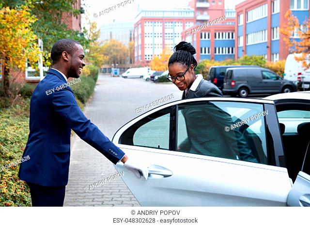 Happy African Male Valet Opening Door For Businesswoman Getting Out Of A Car On Street