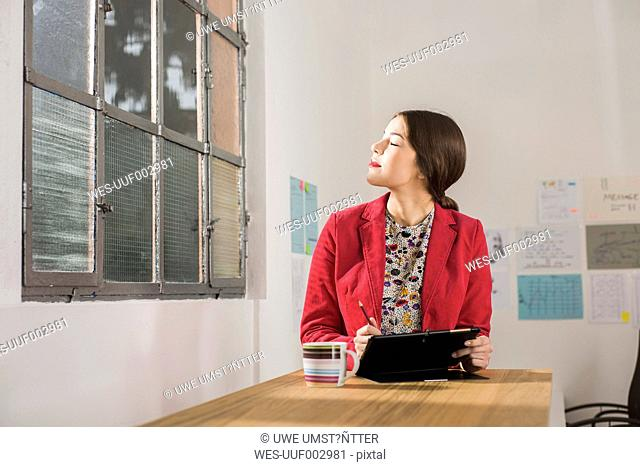 Young businesswoman with digital tablet in office enjoying sunlight