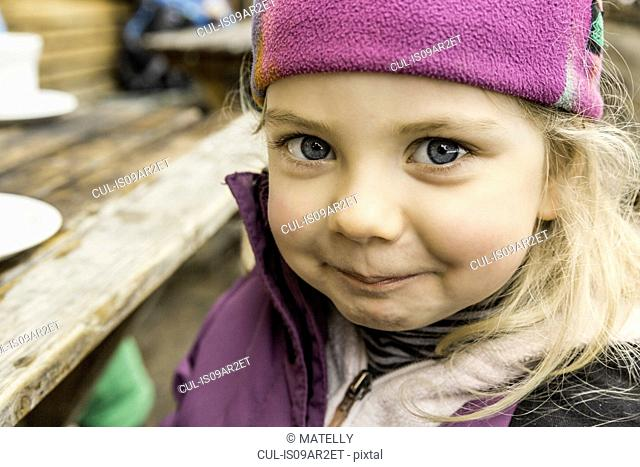 Portrait of young girl in skiwear, smiling, close-up