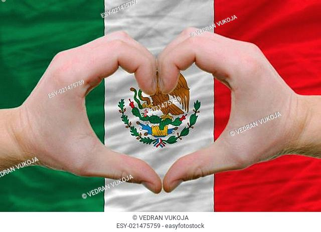 Heart and love gesture showed by hands over flag of mexico backg
