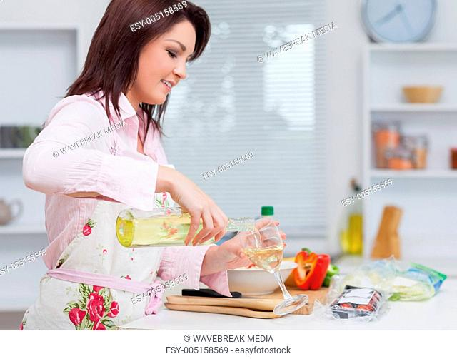 Young woman pouring wine while cooking food