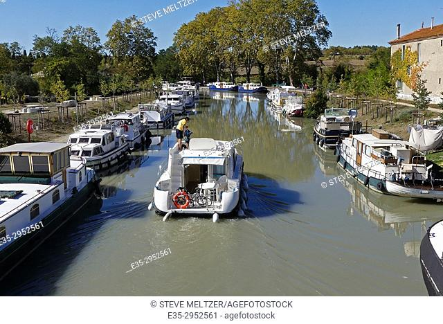 A father and son piloting a boat down the Canal du Midi at Capestang, France