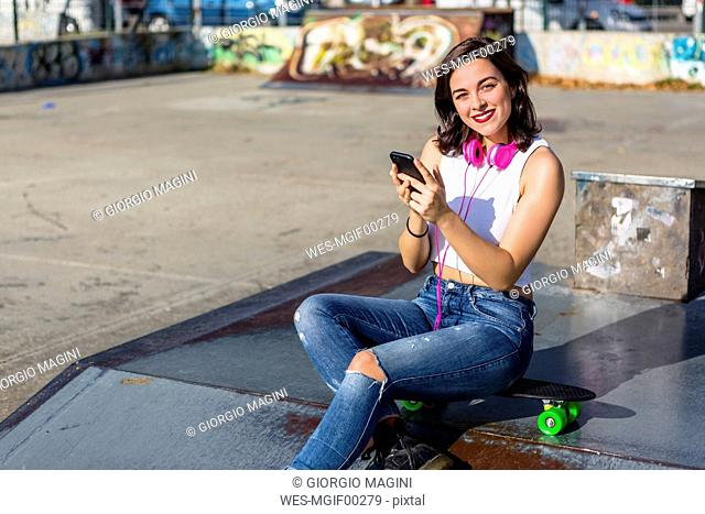 Portrait of smiling young woman with headphones and cell phone at a skatepark