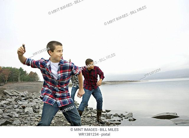 A day out at Ashokan lake. Three boys on the shore throwing skimmers pebbles across the water