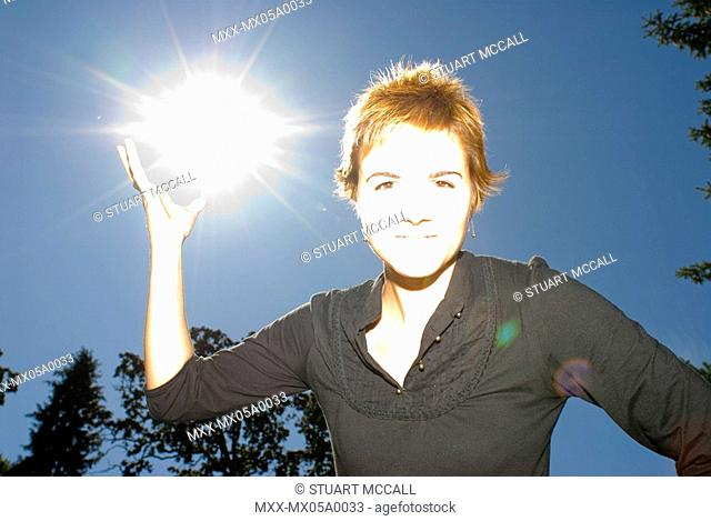 Young woman 30 - 35 holding the sun