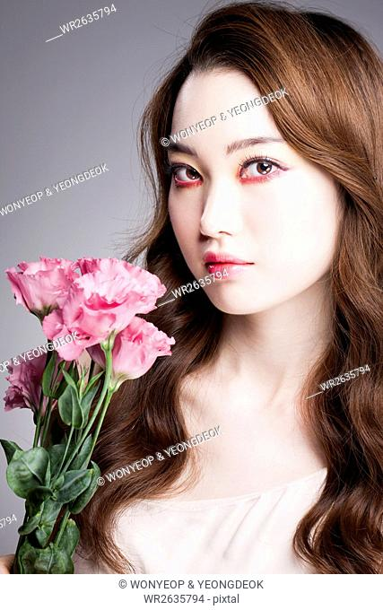 Portrait of young Korean woman in red eye liner with flowers