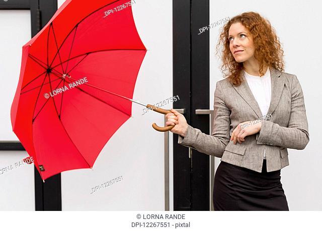 Businesswoman with a red umbrella; Abbotsford, British Columbia, Canada