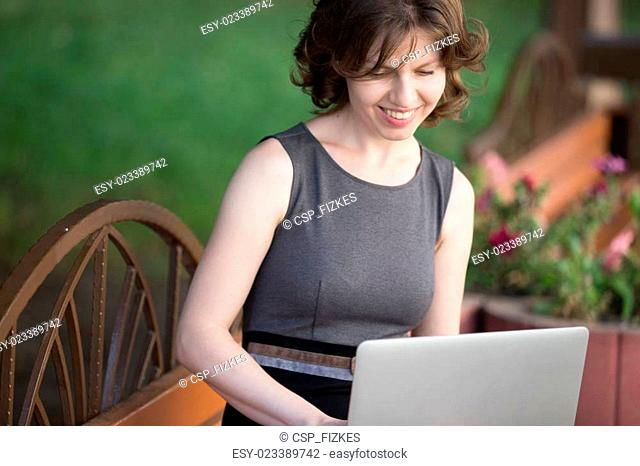 Young woman working on laptop outside