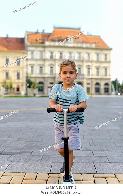Portrait of boy riding a scooter in the city